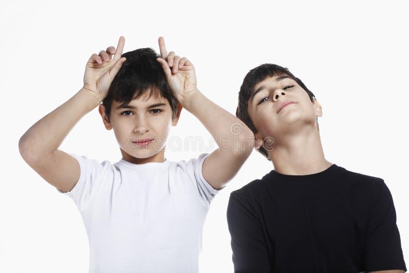 Pojke som visar ohyfsad gest, medan stå med brodern arkivbilder