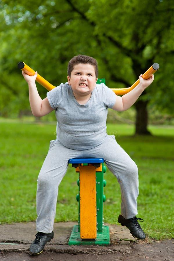 Pojke sport, fett, kondition, övning, unge som är stark, instruktör, viktförlust royaltyfri foto