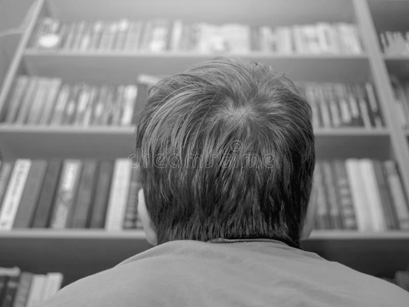 Pojke, studentLooking Up The bokhyllor hemma, skola, arkiv eller en bokhandel Akademisk utbildning, hårt lärande begrepp royaltyfri bild