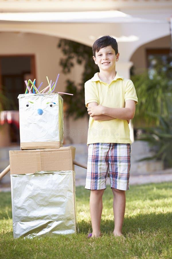Pojkeanseende i trädgård med den hemlagade roboten royaltyfria bilder