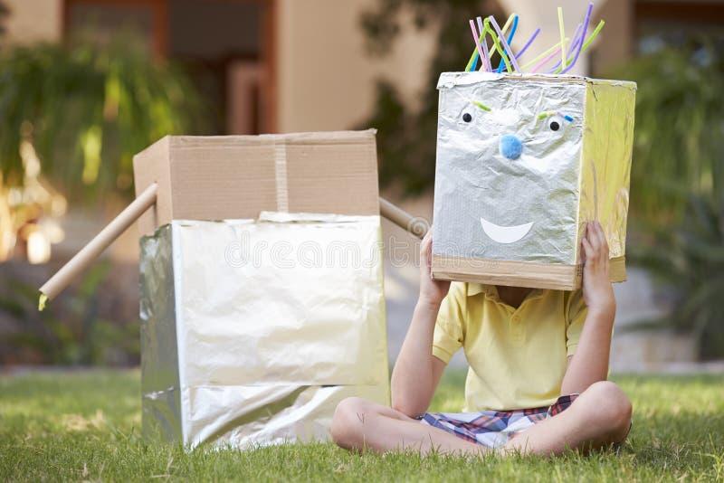 Pojkeanseende i trädgård med den hemlagade roboten arkivfoton