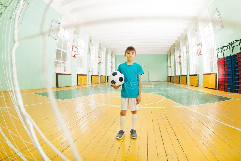 Pojkeanseende med fotbollbollen i skolagymnastiksal royaltyfria foton