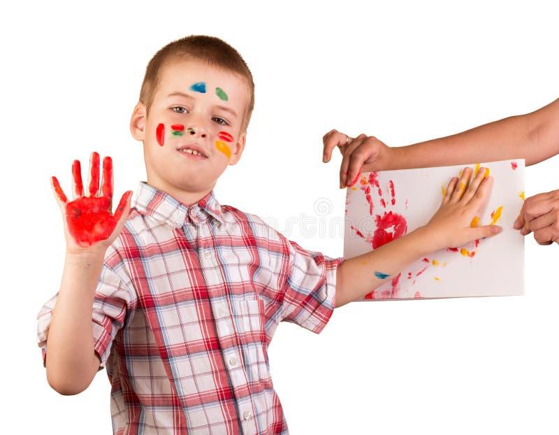 Pojkeattraktioner fingrar målarfärger på arket av papper, hans framsida och händer i målarfärgen som isoleras på vit royaltyfri fotografi