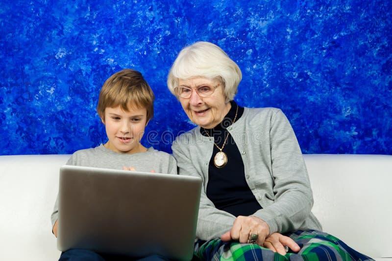 pojkebärbar dator som ser den gammala kvinnan royaltyfri foto