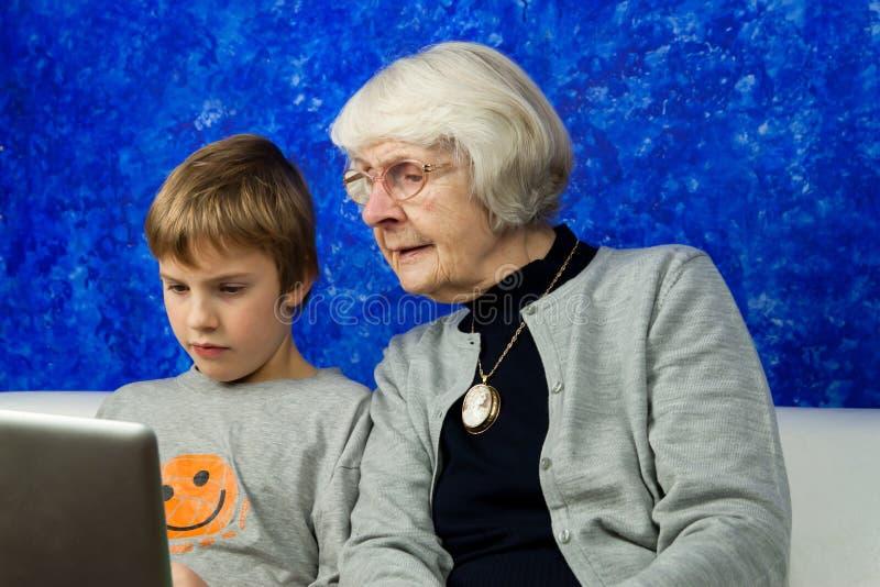 pojkebärbar dator som ser den gammala kvinnan royaltyfri bild