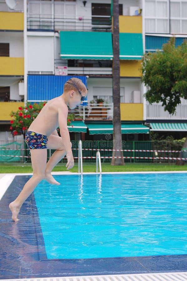 Pojkebanhoppning i kallt vatten av simbassängen arkivbilder