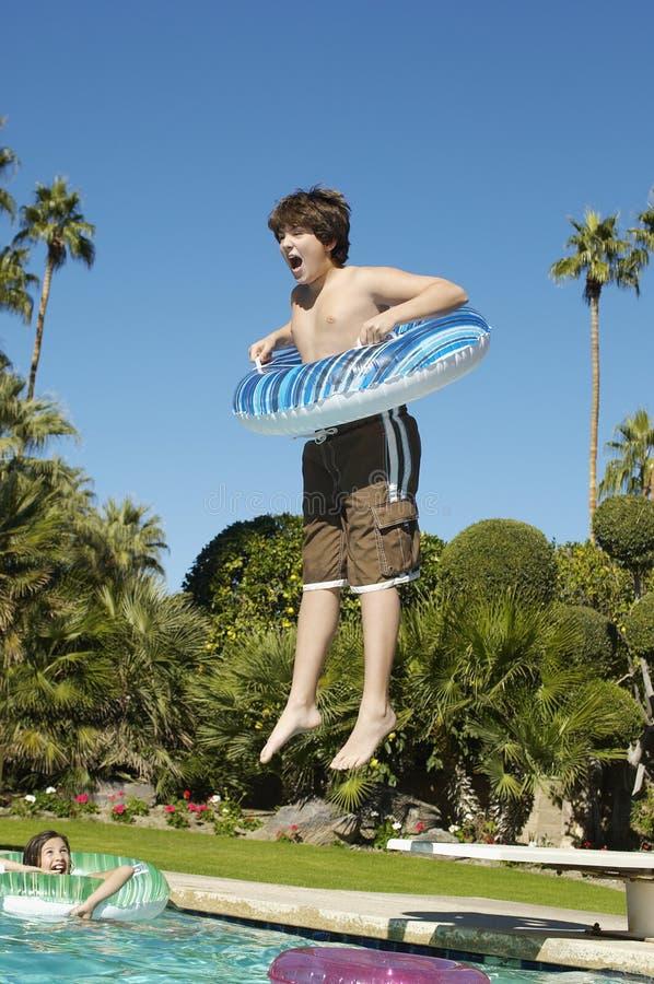 Pojkebanhoppning in i simbassäng fotografering för bildbyråer