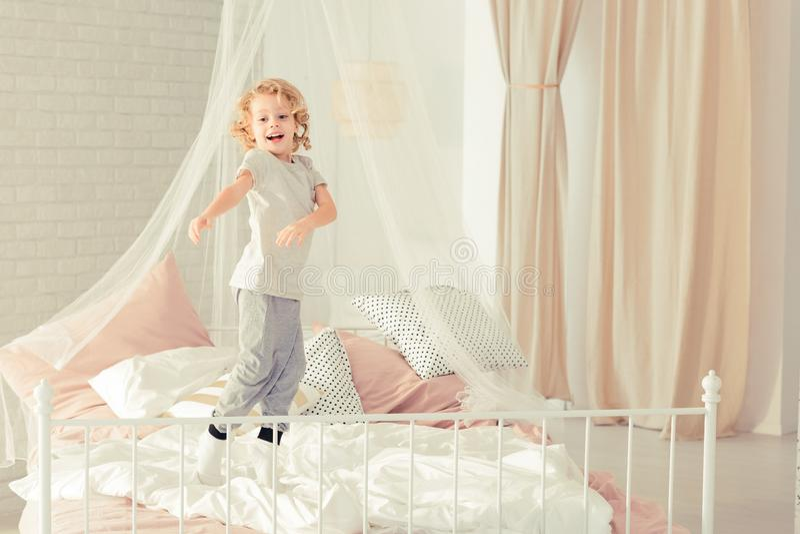 Pojkebanhoppning på sängen royaltyfria bilder