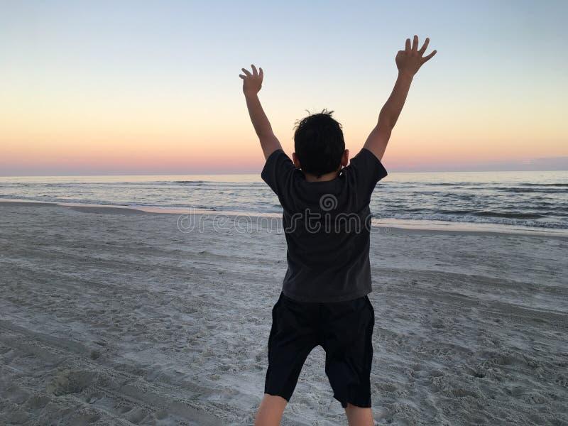 Pojkebanhoppning på strand royaltyfri foto