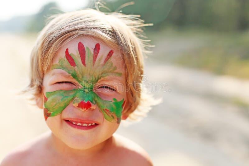Pojkebarn med en maskering på hennes framsida royaltyfri fotografi