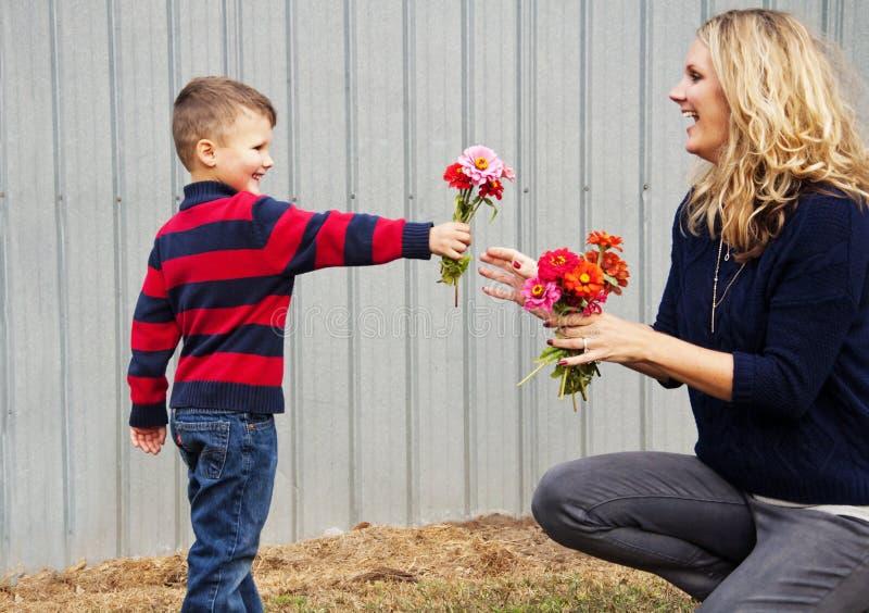 Pojkebarn som ger mammablommor royaltyfri fotografi