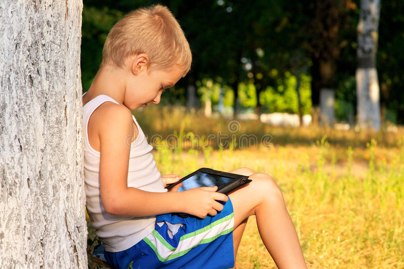 Pojkebarn som spelar med den utomhus- minnestavlaPC:N royaltyfria foton