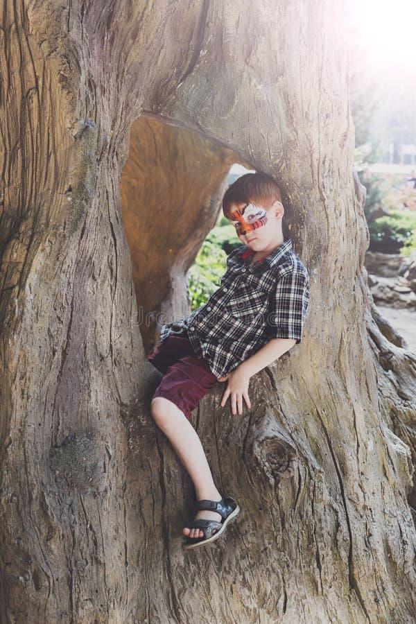 Pojkebarnet sitter utomhus i träd med fjärilsframsidamålning royaltyfri fotografi