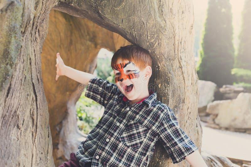 Pojkebarnet sitter utomhus i träd med framsidamålning arkivbilder