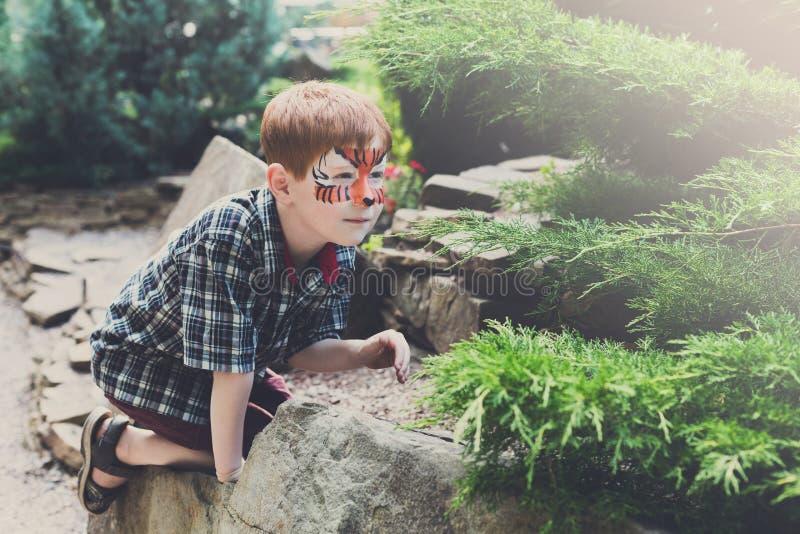 Pojkebarnet spelar utomhus utomhus med framsidamålning arkivbild