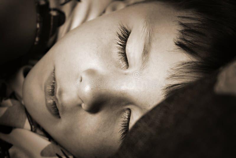 pojkebarnet ta sig en tupplur sova tid royaltyfri bild