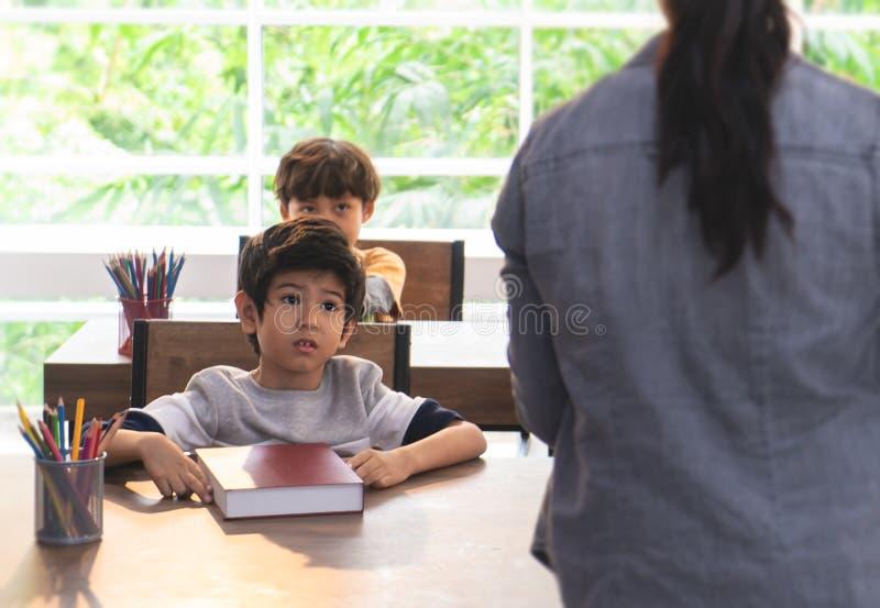 Pojkebekymmer och upp att ställa in i klassrum arkivbilder