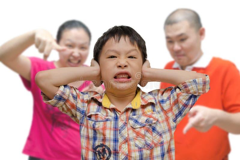 Pojkebeläggningöron, medan föräldrar grälar på honom royaltyfri fotografi
