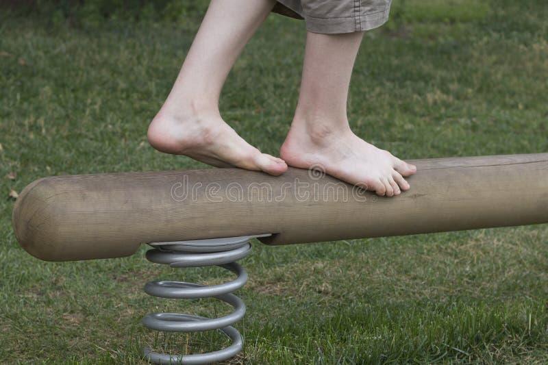 Pojkeben på en balansbom Gå framåt Framgångmoment royaltyfri bild