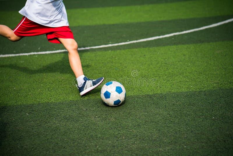 Pojkeben som sparkar fotbollbollcloseupen royaltyfri bild
