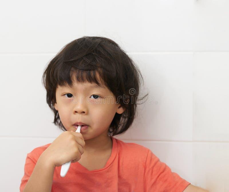 Pojkeborste hans tänder i badrum arkivbild