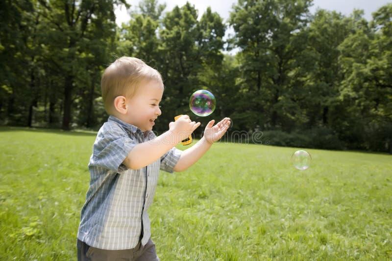 pojkebubblor fångar little tvål arkivfoto