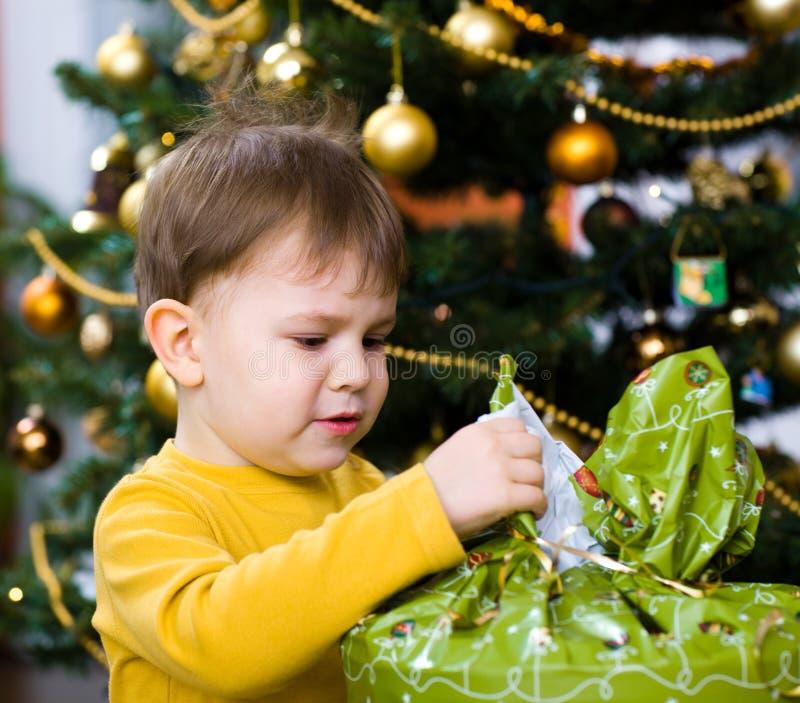 pojkechrismas little öppningspresent fotografering för bildbyråer