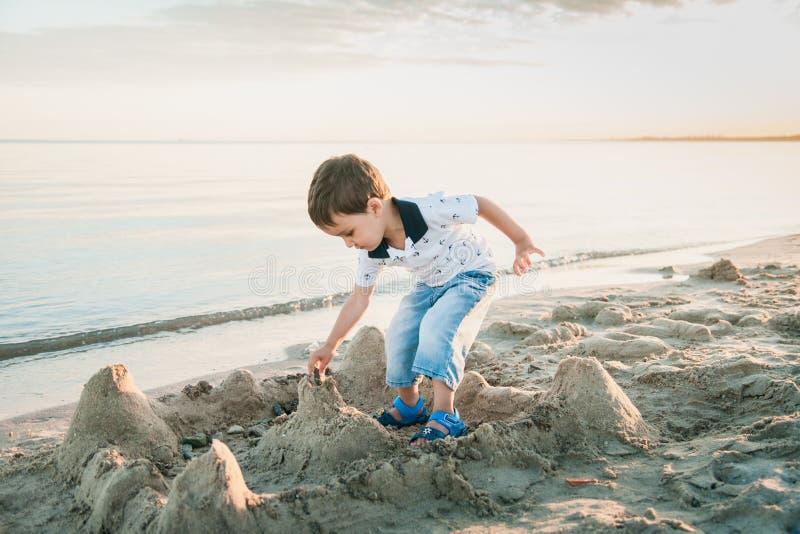 Pojkedanandesandslott på stranden royaltyfri foto