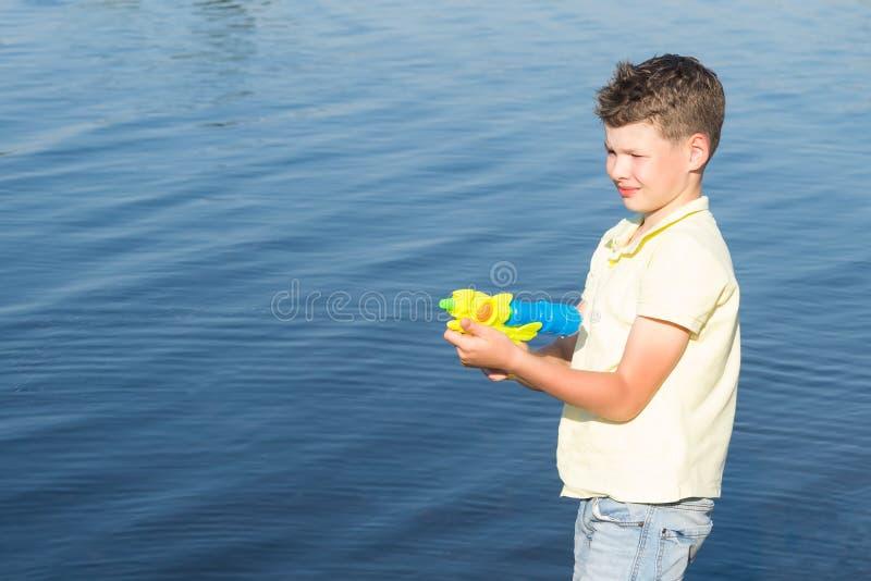 Pojkedet fria av sjön som spelar med ett vattenvapen, vattensprej, sommarlekar royaltyfri fotografi