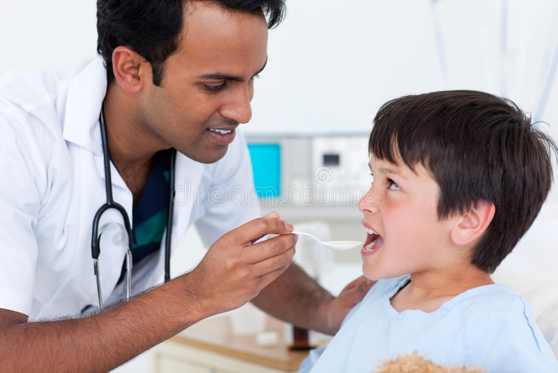 pojkedoktor som ger little medicin till barn fotografering för bildbyråer