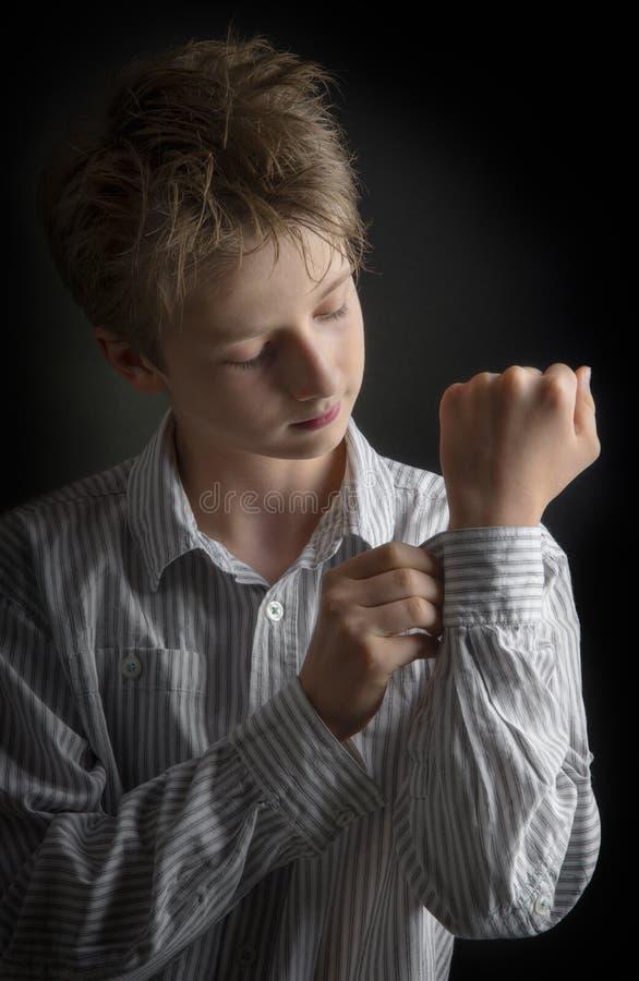 Pojkedressing i mörkret arkivfoton