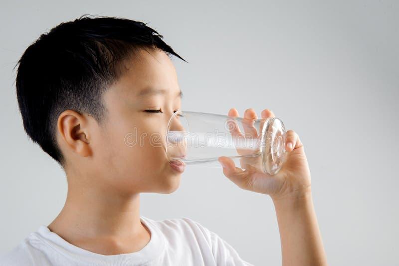 Pojkedrinkvatten från exponeringsglas royaltyfria foton