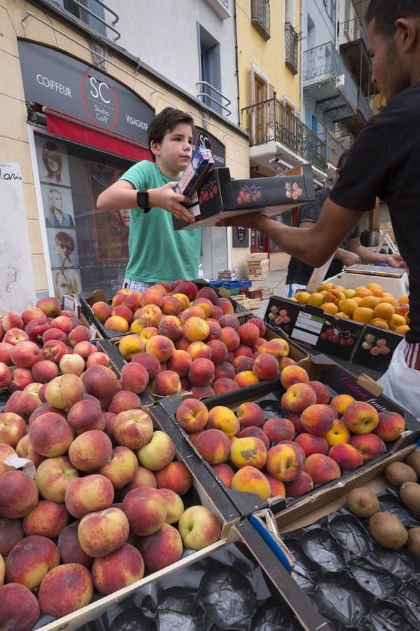 Pojkeförsäljningspersikor och annan frukt på marknad för öppen luft av briancon i den franska haute provencen royaltyfri bild