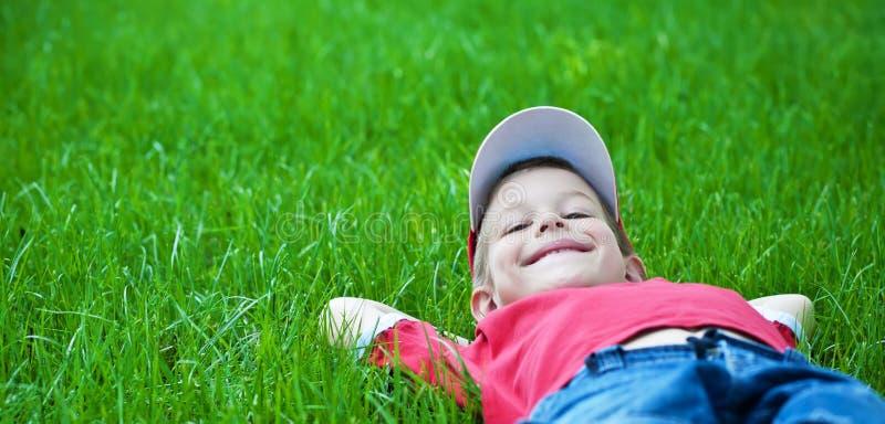 pojkefamiljgräs som lägger parkpicknickfjädern royaltyfria foton