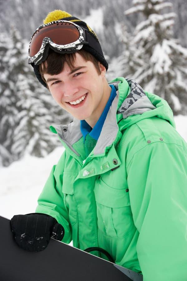 pojkeferie skidar den tonårs- snowboarden royaltyfria bilder