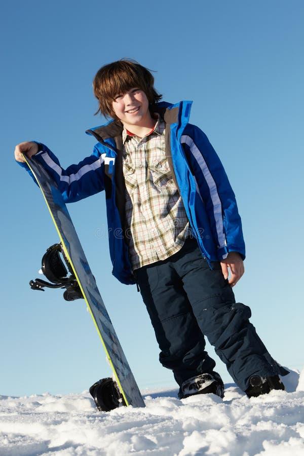pojkeferie skidar snowboardbarn royaltyfria bilder