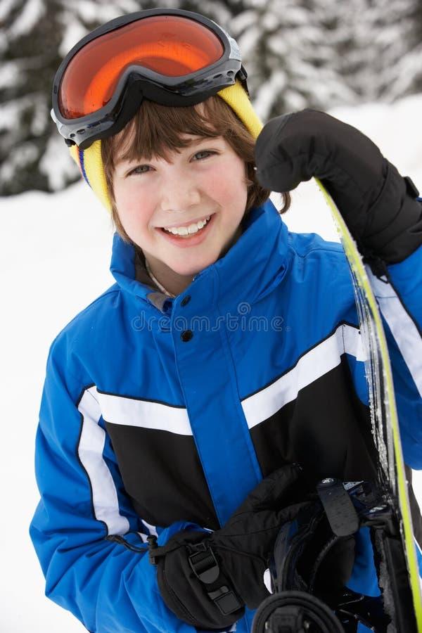 pojkeferie skidar snowboardbarn royaltyfria foton