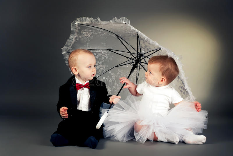 pojkeflicka little sittande paraply under royaltyfria foton