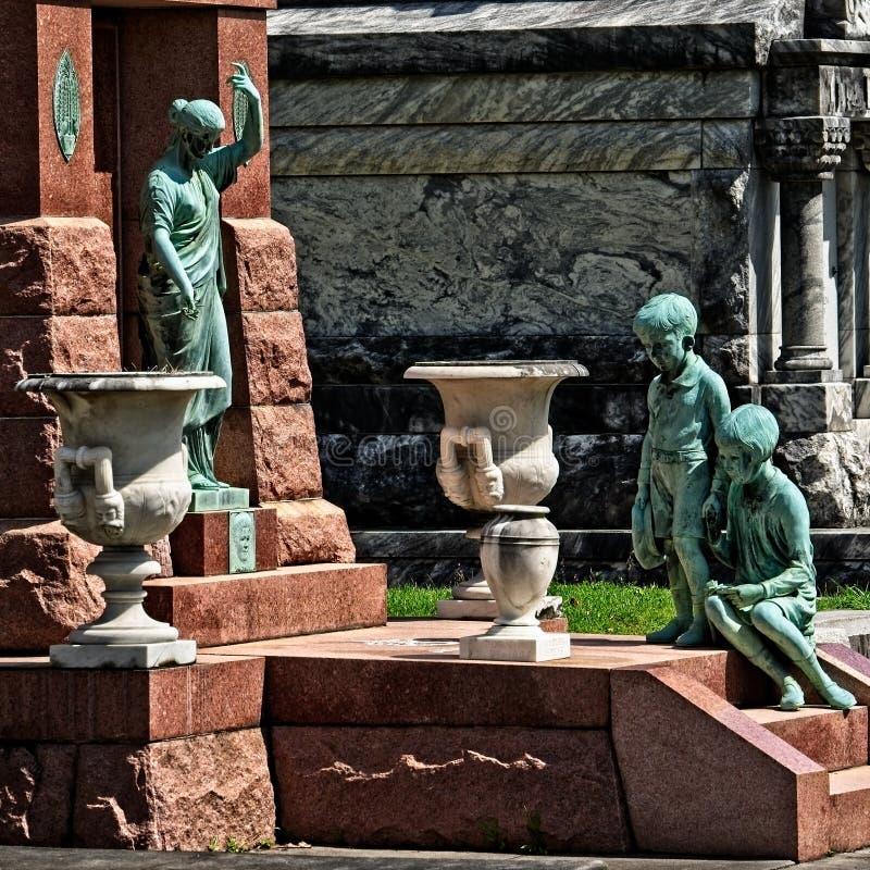 Pojkeflicka och kvinnastaty på gravvalvet royaltyfria foton