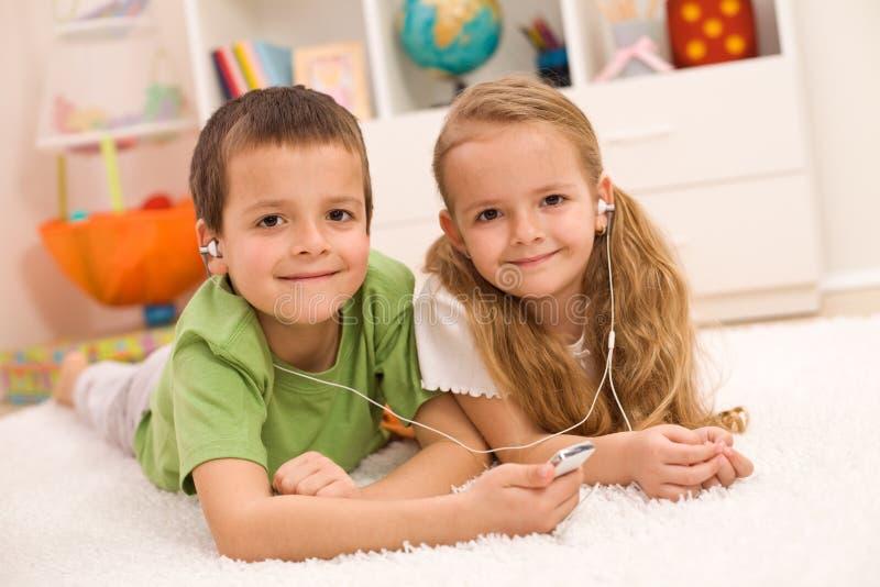 pojkeflicka som lyssnar little musik till tillsammans arkivfoton
