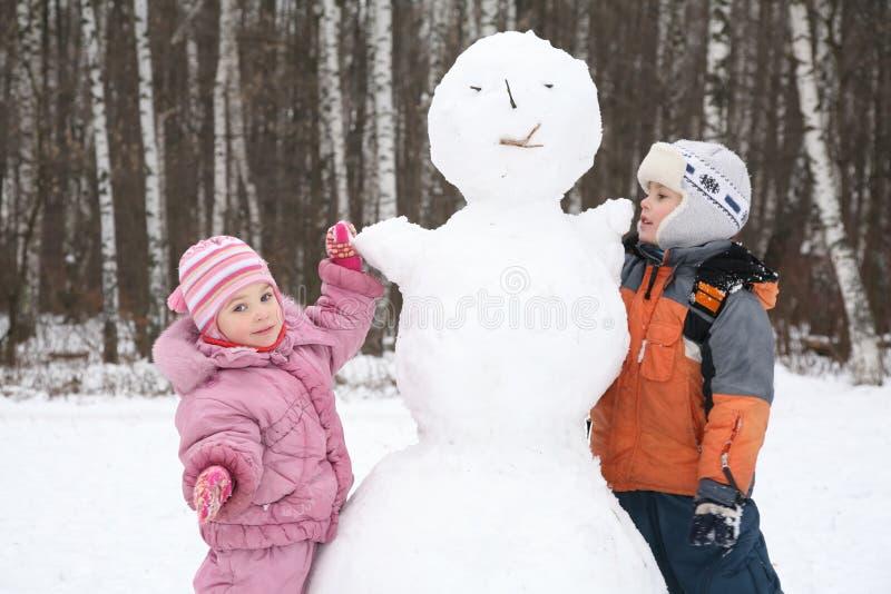 pojkeflickan gör snowmanen fotografering för bildbyråer