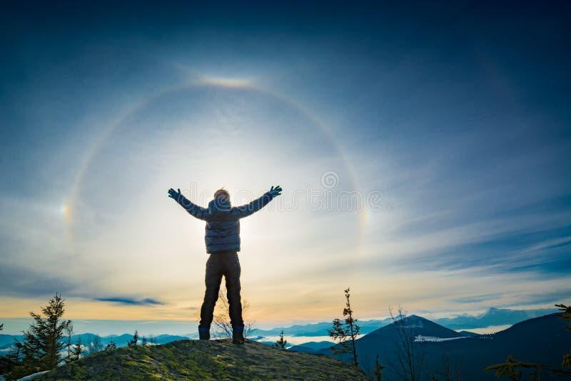 Pojkefotvandrareanseendet med lyftta händer på en överkant av berget royaltyfri bild
