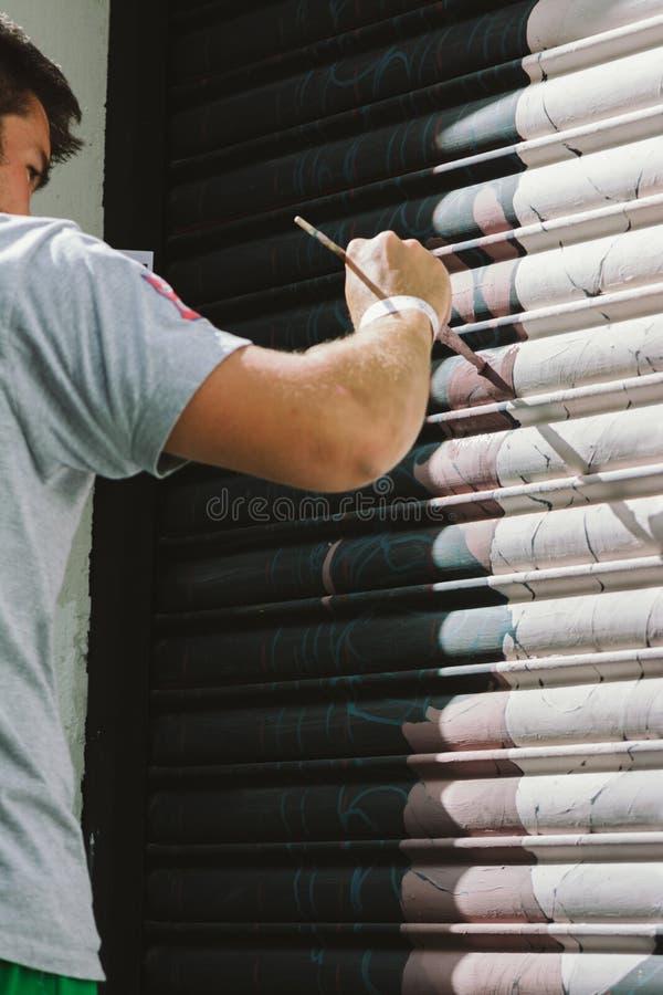 Pojkegrafitti som målas med borsten, på rullgardinen av ett lager royaltyfri foto