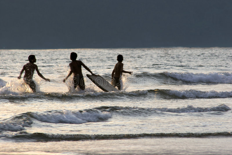 pojkegyckel som har att surfa för solnedgång arkivbilder