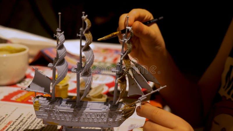 Pojkehänder som hemma monterar den plast- modellsatsen av skeppet Hobby och fritid royaltyfri fotografi
