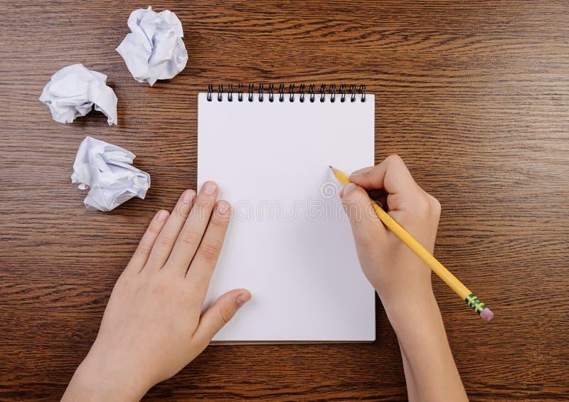 Pojkehandstil i notepad och skrynkliga ark omkring royaltyfri foto