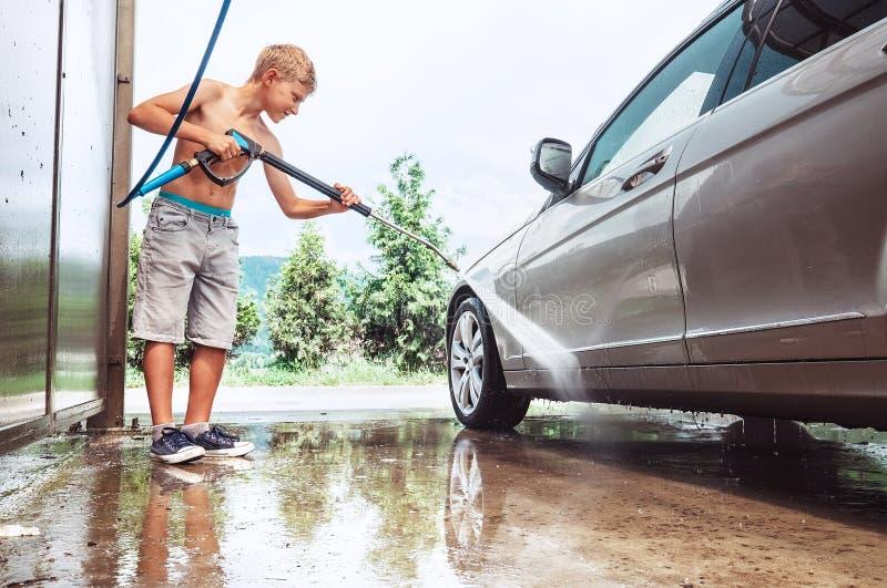 Pojkehjälp som tvättar en bil royaltyfria foton