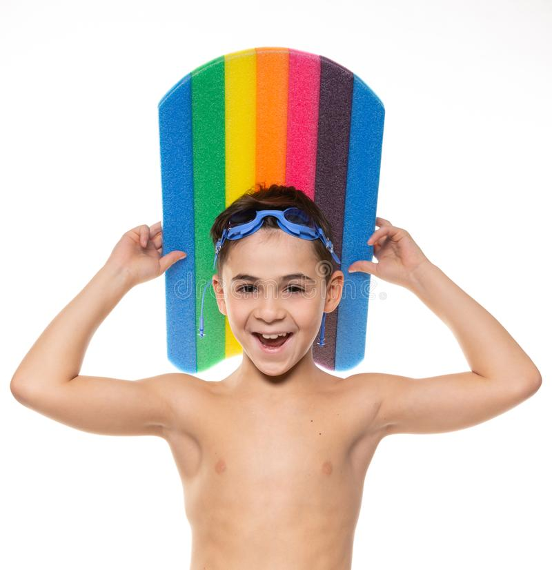 Pojkeidrottsman nen med blå simma skyddsglasögon och ett bräde för att simma ovanför hans huvud, skratt, begrepp, på en vit bakgr royaltyfri bild
