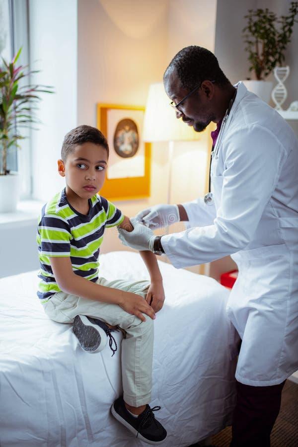 Pojkekänsla som skrämmas för injektion, medan besöka doktorn arkivfoto