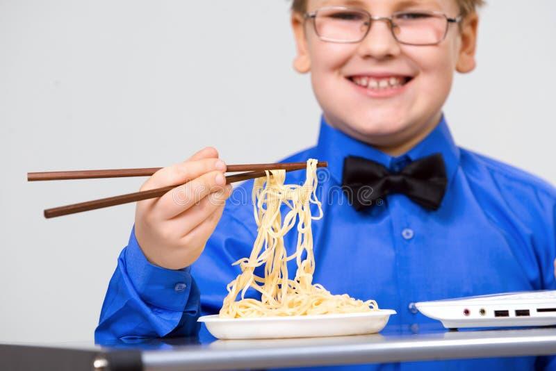pojkekines som äter hungriga nudelsticks royaltyfri fotografi